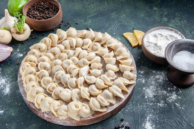 Vue de face petites boulettes avec de la farine sur une surface gris foncé