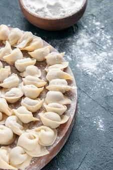 Vue de face petites boulettes avec de la farine sur une surface sombre