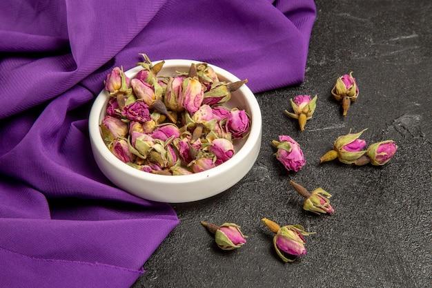 Vue de face de petites fleurs violettes avec du tissu violet sur un espace gris