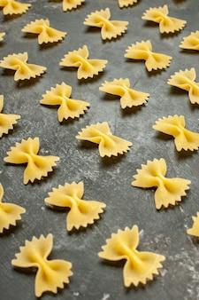 Vue de face de petites pâtes crues bordées de gris foncé de nombreux aliments photo couleur pâte repas pâtes italiennes