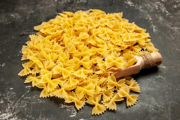 Vue de face petites pâtes crues sur photo couleur gris foncé beaucoup de pâte à pâtes italiennes