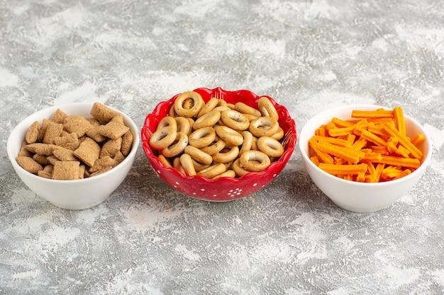 Vue de face petits biscuits et craquelins doux oreillers avec biscottes sur surface blanche