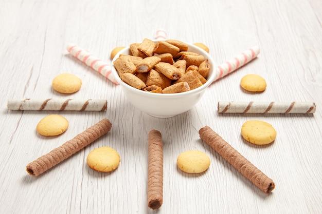Vue de face de petits biscuits d'oreiller avec des biscuits sur du sucre de biscuit de biscuit de bureau blanc