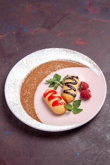 Vue de face de petits biscuits sucrés à l'intérieur d'une assiette conçue sur un espace sombre