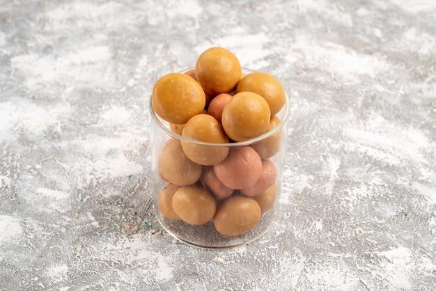 Vue de face petits bonbons sur un espace blanc