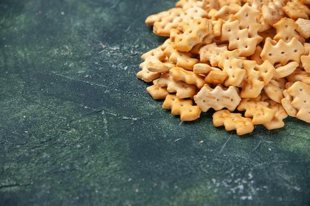 Vue de face petits craquelins sur fond gris foncé croustillant sel poivre couleur snack pain cips