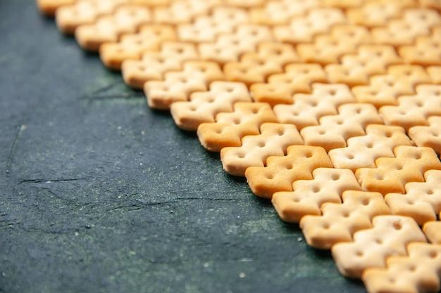 Vue de face petits craquelins sur fond sombre couleur croquante collation pain de sel biscotte sèche nourriture cips