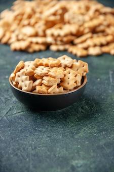 Vue de face de petits craquelins salés à l'intérieur de la plaque sur le fond sombre couleur croquante collation cips sel poivre pain biscotte sèche nourriture