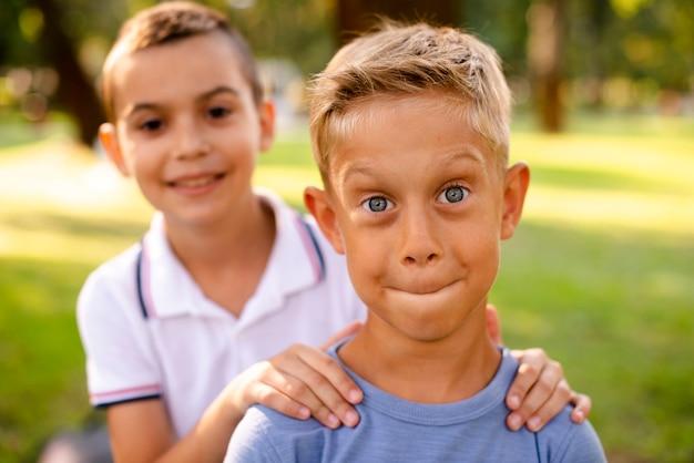Vue de face des petits garçons faisant des grimaces idiotes pour la caméra