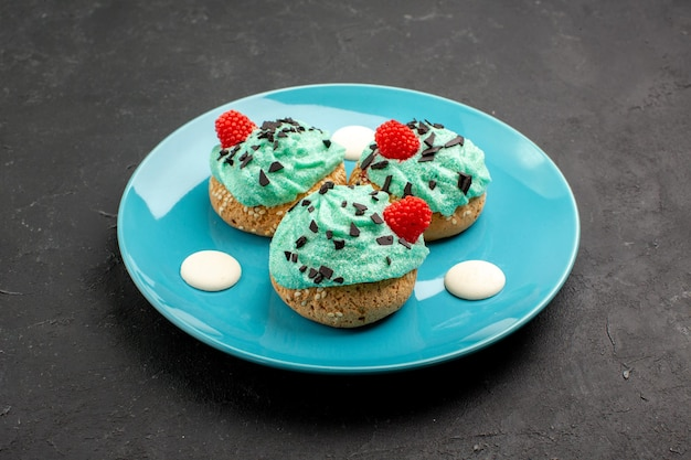 Vue de face petits gâteaux crémeux délicieux bonbons pour le thé à l'intérieur de la plaque sur fond sombre gâteau à la crème biscuit dessert couleur du thé