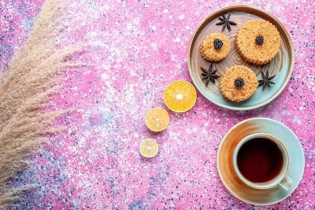 Vue de face de petits gâteaux délicieux doux et délicieux à l'intérieur de la plaque avec du thé sur la surface rose
