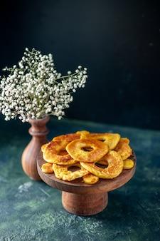 Vue de face de petits gâteaux délicieux en forme d'anneau d'ananas sur une tarte aux fruits noirs