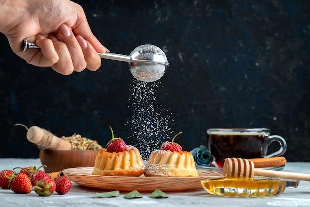Une vue de face petits gâteaux délicieux avec des fraises rouges, cannelle et biscuit gâteau au thé
