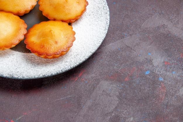 Vue de face petits gâteaux délicieux à l'intérieur de la plaque sur fond sombre biscuits à tarte sucrée biscuits au thé gâteau