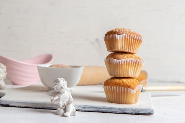 Vue de face de petits gâteaux à l'intérieur de formulaires papier avec du sucre en poudre sur la surface blanche