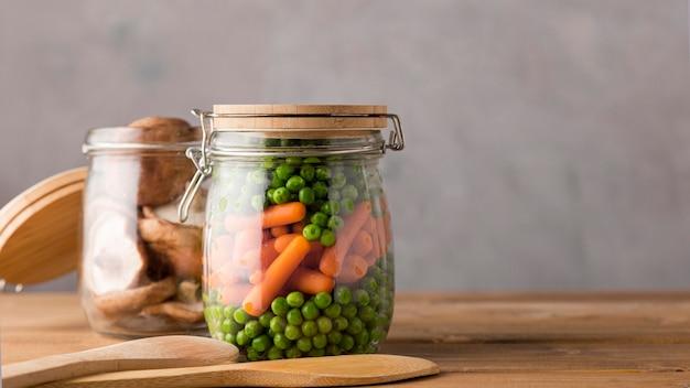 Vue de face des petits pois et carottes dans un bocal en verre avec espace de copie