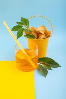 Une vue de face physalises pelées orange à l'intérieur du seau avec un cocktail sur le bureau jaune-bleu
