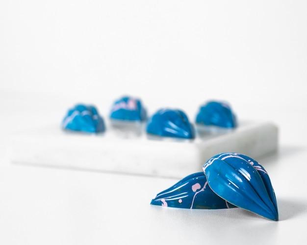 Vue de face des pierres bleues sur et à l'extérieur de l'éponge blanche sur le bureau blanc