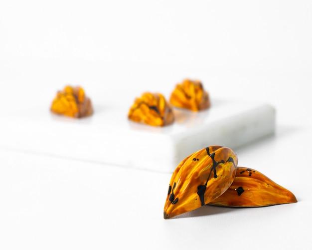 Vue de face pierres colorées peu conçues en jaune sur l'éponge et la surface blanches