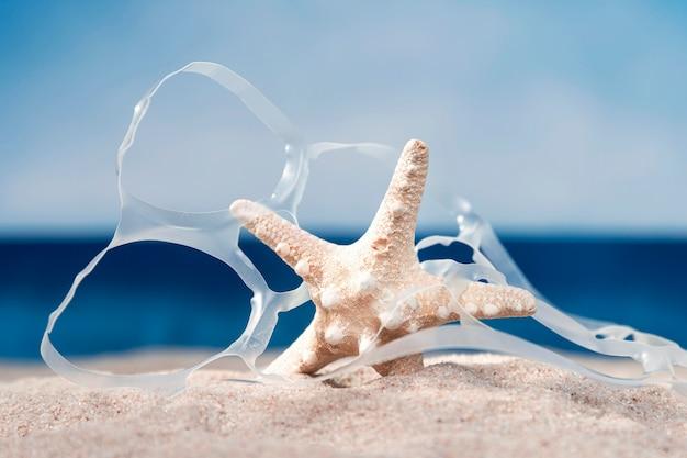 Vue de face de la plage avec des étoiles de mer et du plastique
