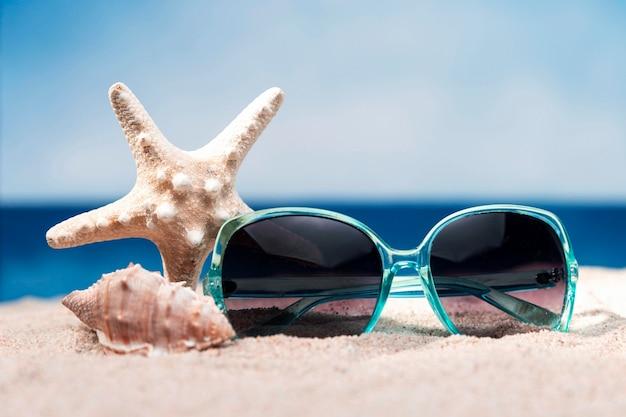 Vue de face de la plage avec des lunettes de soleil et des étoiles de mer