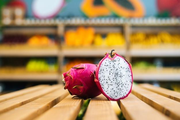 Vue de face de plan rapproché de pitahaya juteux frais se tenant sur la palette en bois à la section de fruits et légumes