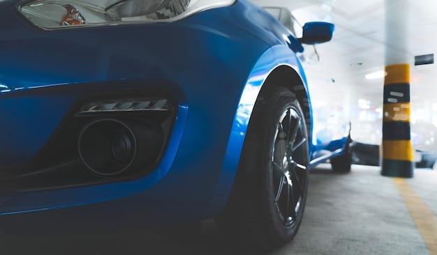 Vue de face de plan rapproché de voiture de suv de luxe bleue garée au parking souterrain de voiture de suv de construction