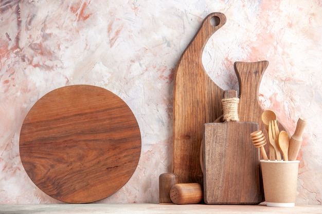 Vue de face de planches à découper brunes en bois de différentes tailles et formes, debout sur le mur sur une surface colorée