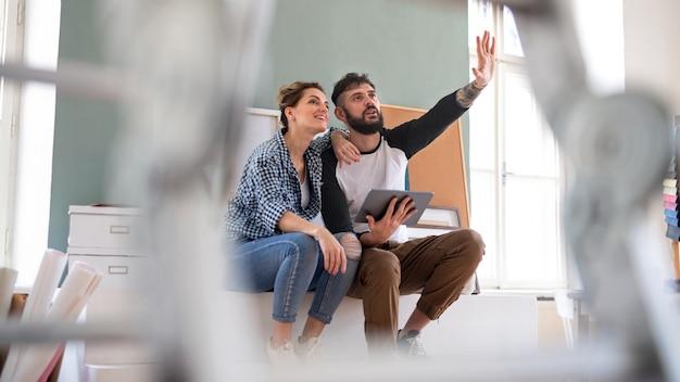 Vue de face de la planification d'un couple d'adultes avec une tablette à l'intérieur à la maison, déménagement et concept de bricolage.