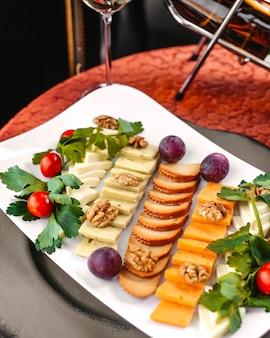 Une vue de face des plats en tranches différents plats à l'intérieur de la plaque blanche sur la table