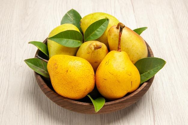 Vue de face poires douces fraîches fruits sucrés à l'intérieur de la plaque sur des fruits de bureau blanc jaune frais sucré mûr