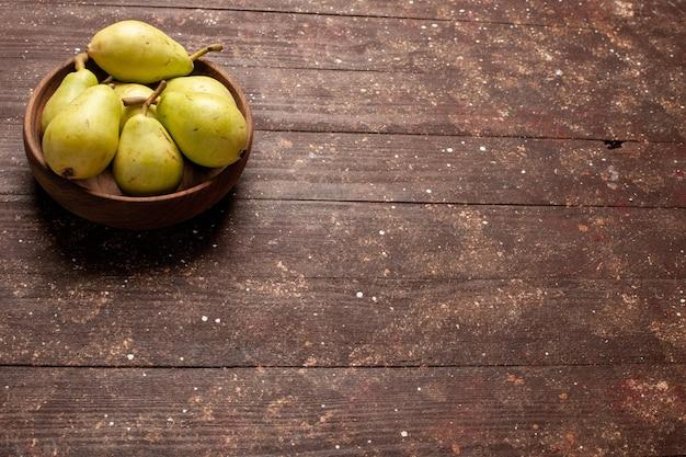 Vue de face poires moelleuses fraîches vertes et juteuses sur l'espace brun