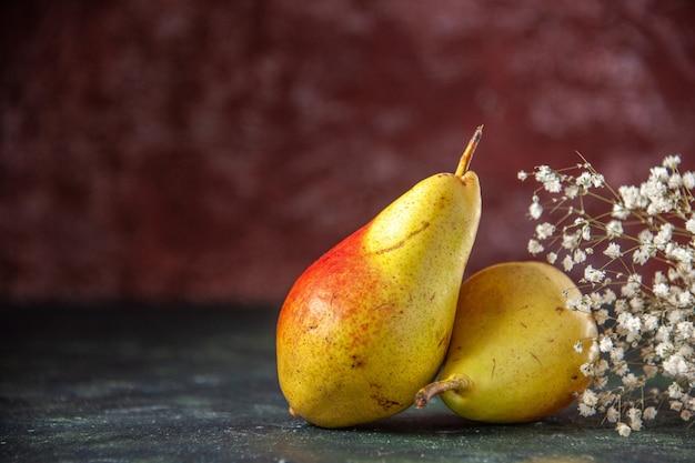 Vue de face poires sucrées sur le fond sombre arbre moelleux jus de pomme fraîche de couleur pulpe mûre