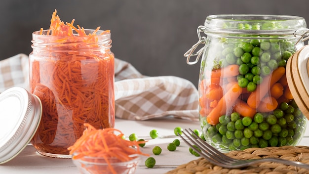 Vue de face des pois marinés et des carottes dans des bocaux transparents