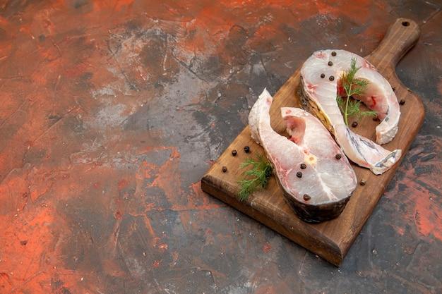 Vue de face de poissons crus frais et de poivre sur une planche à découper en bois sur le côté gauche sur une surface de couleur mélangée avec un espace libre