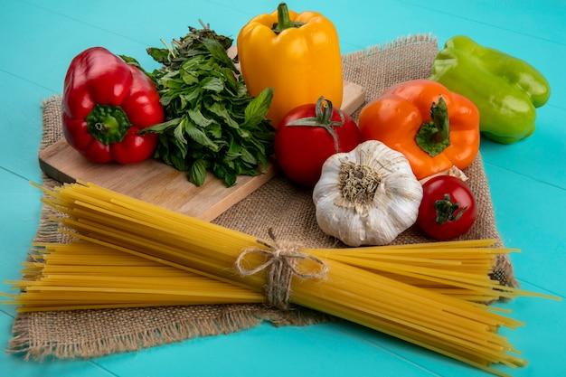 Vue de face de poivrons colorés sur une planche à découper avec des spaghettis crus à la menthe et l'ail sur une surface turquoise