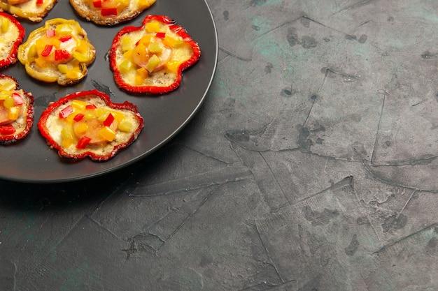 Vue de face poivrons cuits pour le déjeuner à l'intérieur de la plaque sur une surface sombre