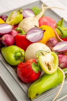 Vue de face poivrons frais avec radis et oignons sur le légume blanc couleur poivre salade mûre vie saine repas photo