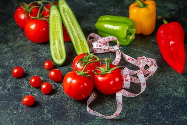 Vue de face des poivrons tomates fraîches et des concombres sur une surface de couleurs foncées avec un espace libre