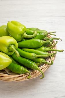 Vue de face de poivrons verts épicés avec des poivrons à l'intérieur du panier sur fond blanc couleur chaude salade de légumes énervée photo mûre