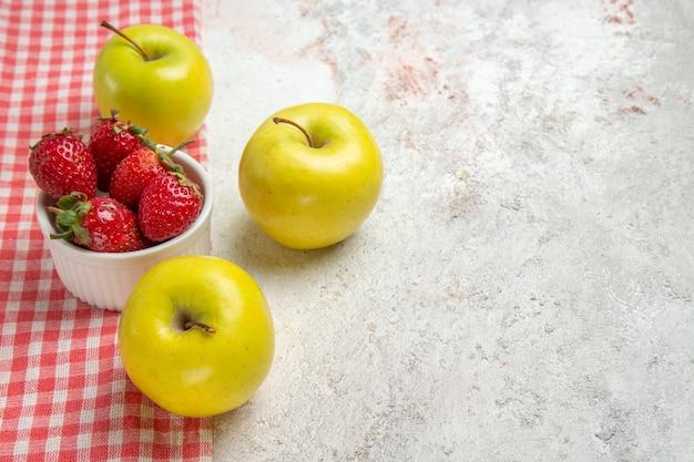 Vue de face des pommes fraîches avec des baies rouges sur une table blanche couleur baies de fruits