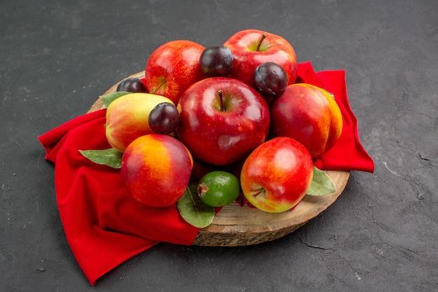 Vue de face des pommes fraîches avec des pêches et des prunes sur un bureau sombre, un arbre à jus mûr et moelleux