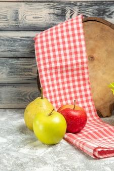 Vue de face pommes fraîches à la poire sur fond gris fruit pomme douce fraîche