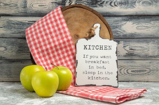 Vue de face des pommes fraîches avec une serviette et une écriture amusante sur le bureau sur fond gris, fruit frais mûr, plante d'arbre moelleux