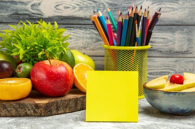 Vue de face des pommes fraîches avec des tranches d'oranges et des crayons sur fond gris fruits mûrs mûrs pomme fraîche