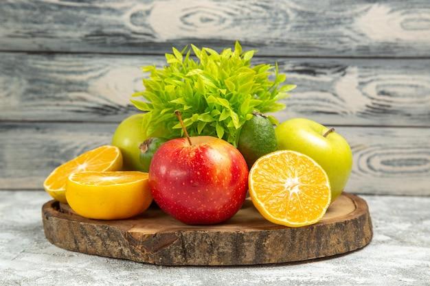Vue de face pommes fraîches avec des tranches d'oranges sur fond gris fruits mûrs mûrs pomme fraîche
