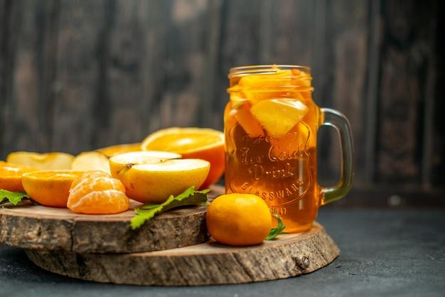 Vue de face des pommes oranges coupées en cocktail sur fond sombre