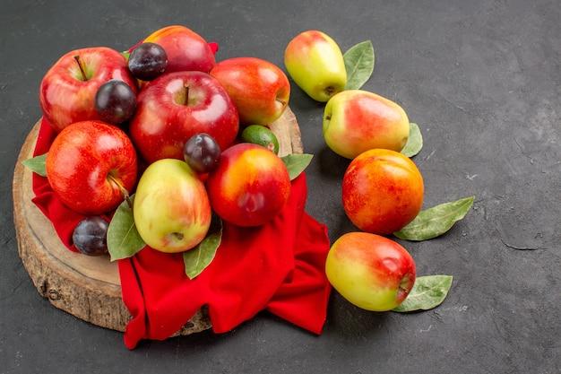 Vue de face des pommes et des prunes fraîches sur le jus de table sombre mûr et moelleux