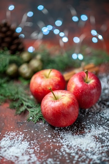 Vue de face pommes rouges bâtons de cannelle poudre de noix de coco sur noir