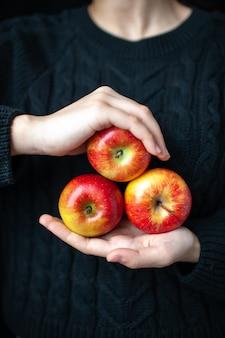 Vue de face des pommes rouges mûres dans les mains des femmes